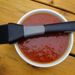 Top view of a bowl of barbeque sauce with a silicone brush