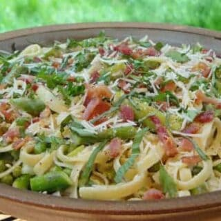 a bowl of fettuccine pasta with asparagus, bacon, peas, and cheese