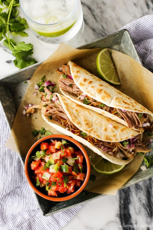 Carnitas recipe from afarmgirlsdabbles.com - Pork is seasoned with oregano, cumin, and paprika, and then braised nice and slow, until it's fall-apart tender. Served with warm tortillas and favorite taco toppings and condiments. #pork #carnitas #mexican #taco