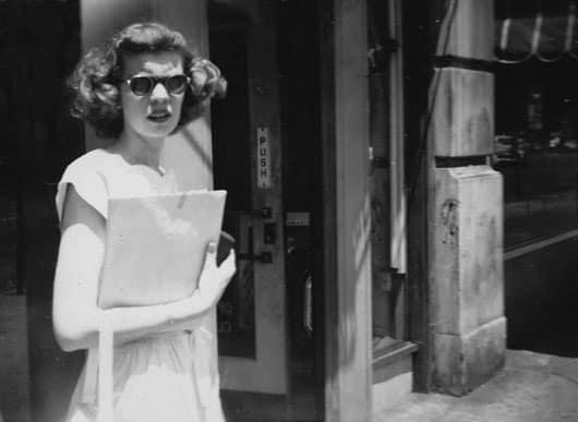 a woman in a dress wearing sunglasses