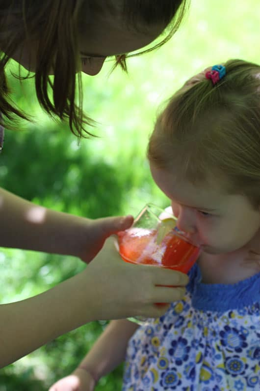 a girl drinking a glass of strawberry lemonade