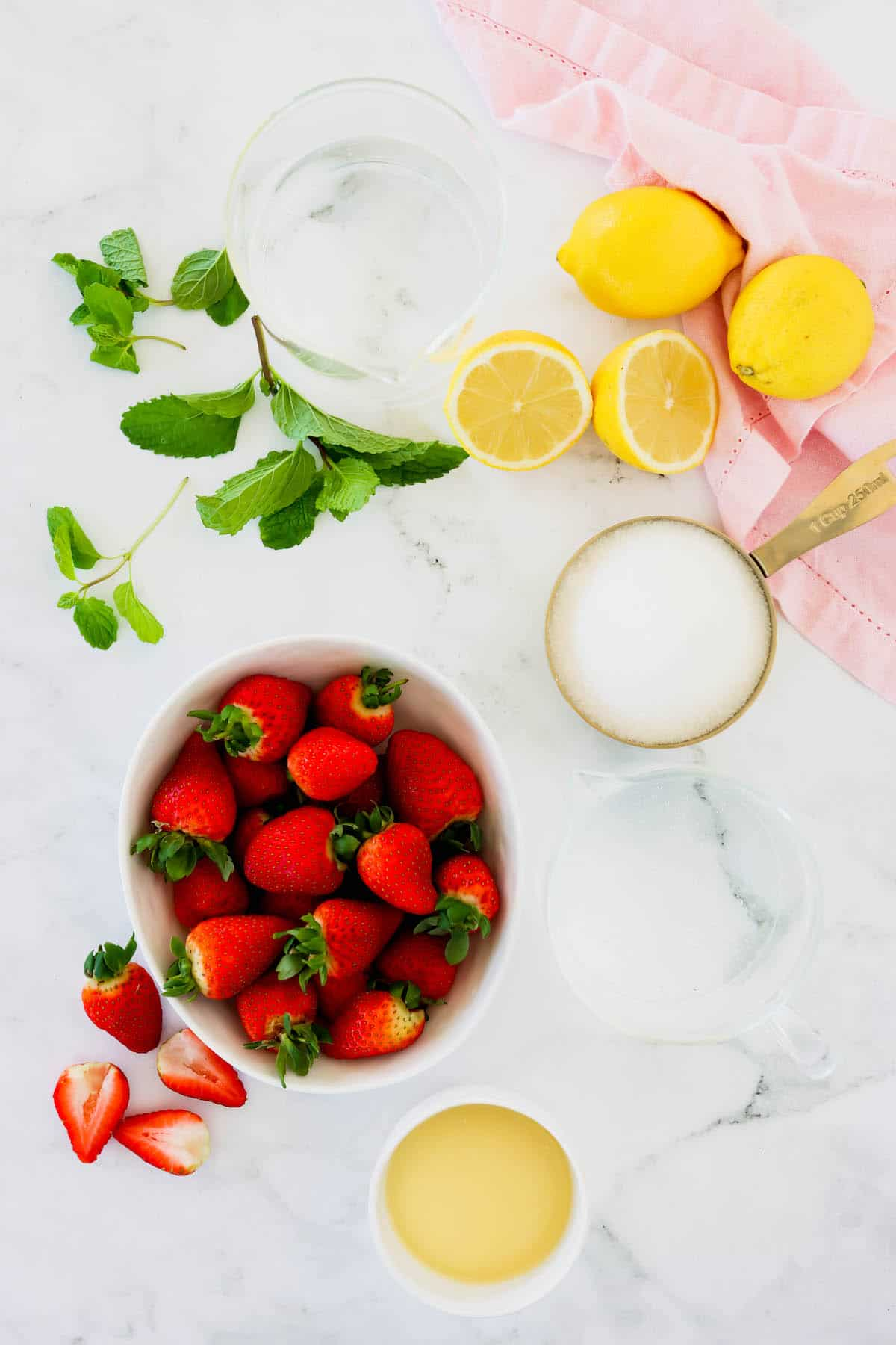 Overhead view of fresh strawberries in a bowl, a measuring cup of sugar and fresh lemons