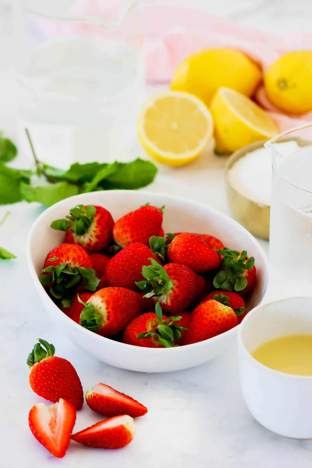 Fresh strawberries in a bowl with lemons in the background