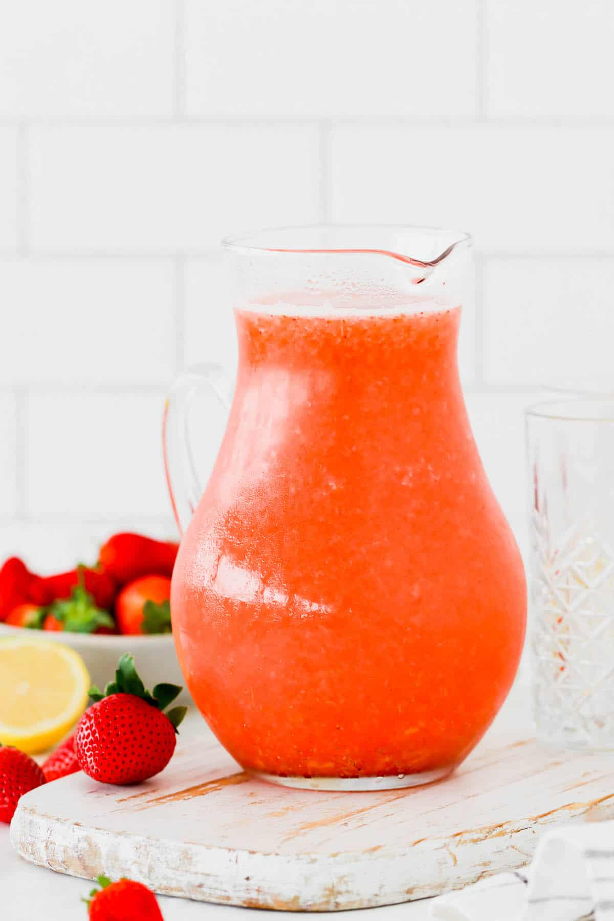 A glass pitcher of homemade strawberry lemonade