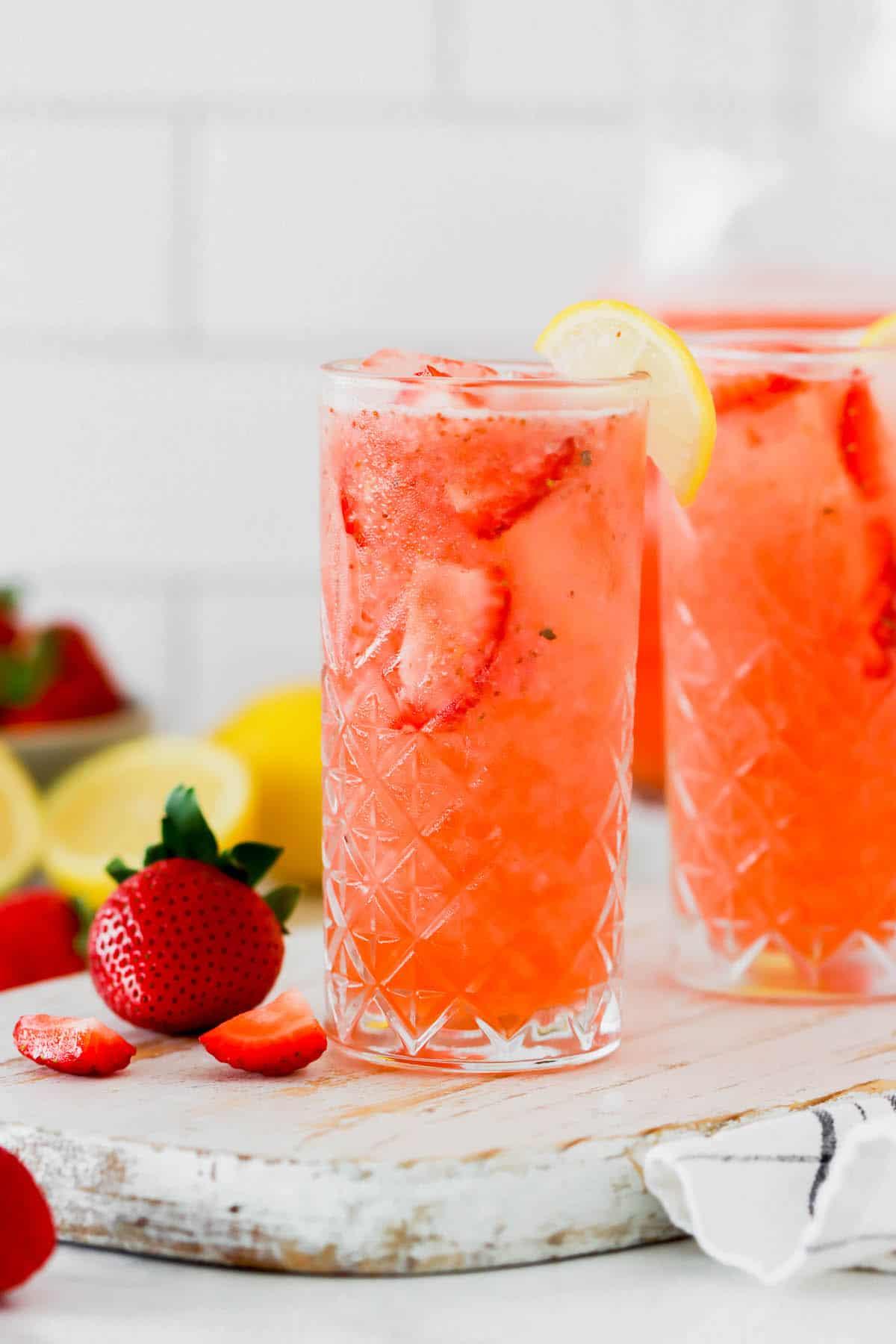 Two glasses of homemade lemonade with strawberries