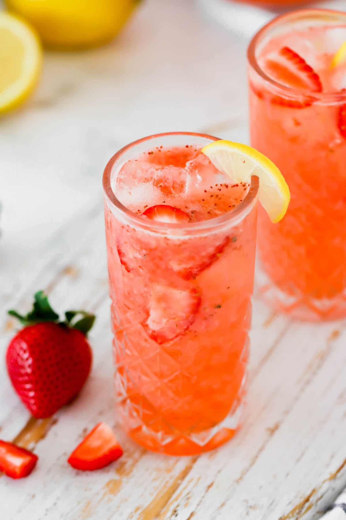 A glass of fresh strawberry lemonade with a lemon wedge