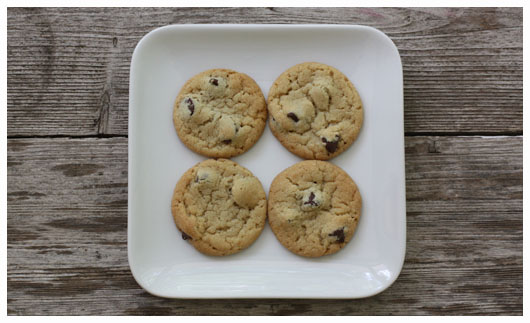 Top view of four chocolate chip cookies on a white square plate