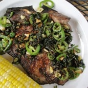 Grilled T-bone steak topped with jalapeno slices and chopped cilantro next to an ear of corn on a white plate