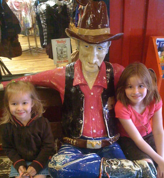 our girls with a cowboy statue