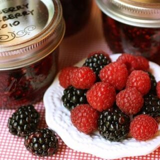 jars of raspberry and blackberry jam with fresh berries