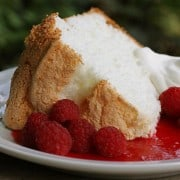 A slice of Angel Food Cake on a plate with berry sauce and fresh raspberries