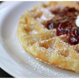 a waffle with jam and whipped cream