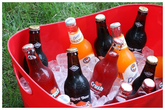 a red bucket filled with ice and bottles of pop