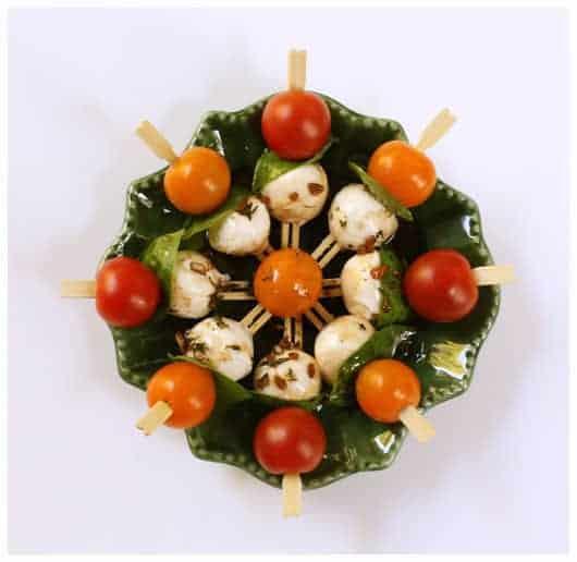 Mini kabobs with cherry tomato, basil, and mozzarella balls arranged in a round dish