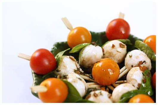 a green plate of caprese kebabs