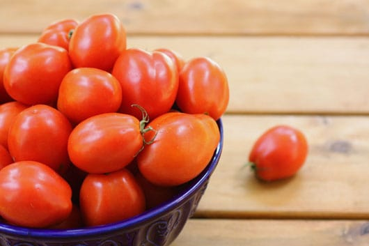 Fresh plum tomatoes in a blue bowl
