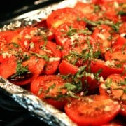 Fresh tomatoes on a foil lined baking sheet with basil