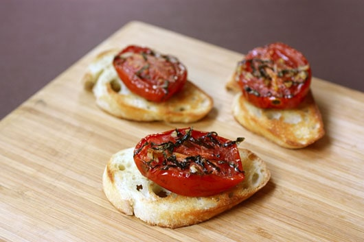 Slices of roasted tomatoes on top of crusty bread