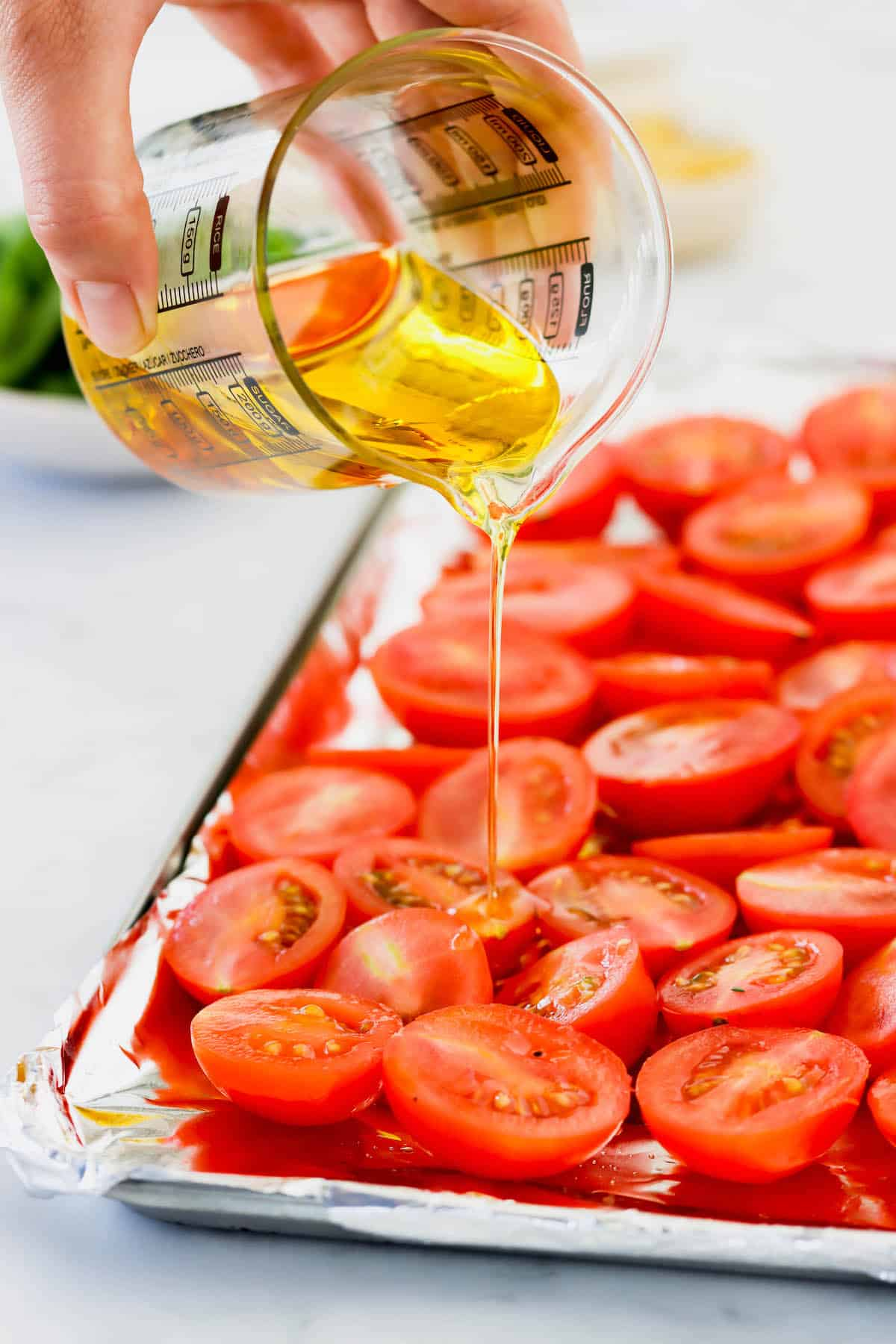 Olive oil being poured over a sheet pan of halved plum tomatoes