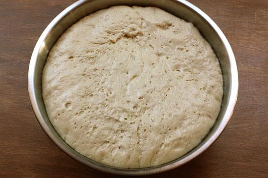 a bowl of risen pizza dough