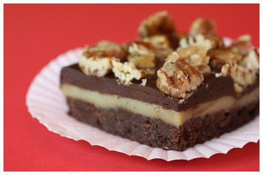 a layered brownie topped with chopped pecans