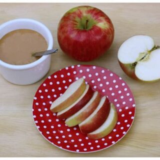 a plate of apple slices and a dish of caramel sauce