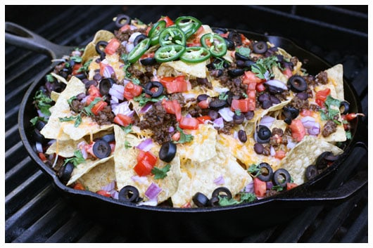 a skillet of nachos on the grill