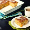 A slice of peach cake on a white plate next to a cup of coffee