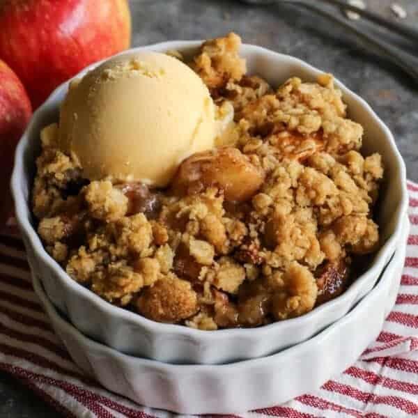 apple crisp in bowl with scoop of vanilla ice cream