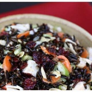 turkey, carrots, celery, cranberries, and wild rice mixed together in a bowl