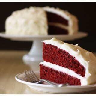 a slice of red velvet cake taken out of a whole cake