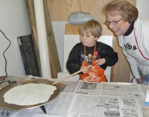 a kid and his grandma making lefse