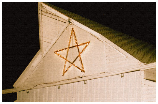 light-up star on a white barn