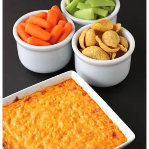 Buffalo chicken dip and some dippers in white bowls