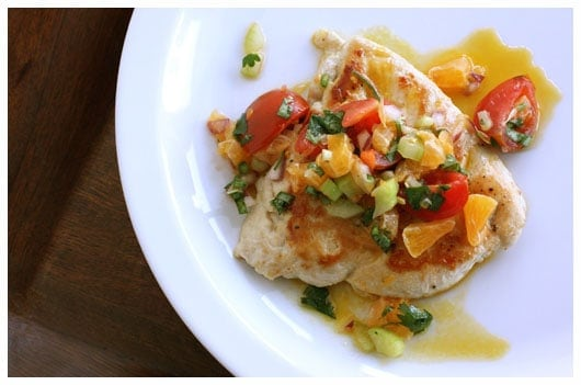 Chicken breast topped with clementine salsa on a white plate