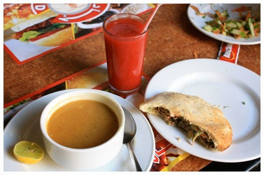 a bowl of lentil soup, shawarma, and a glass of strawberry juice
