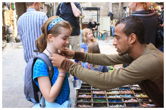 a man putting a necklace on a girl
