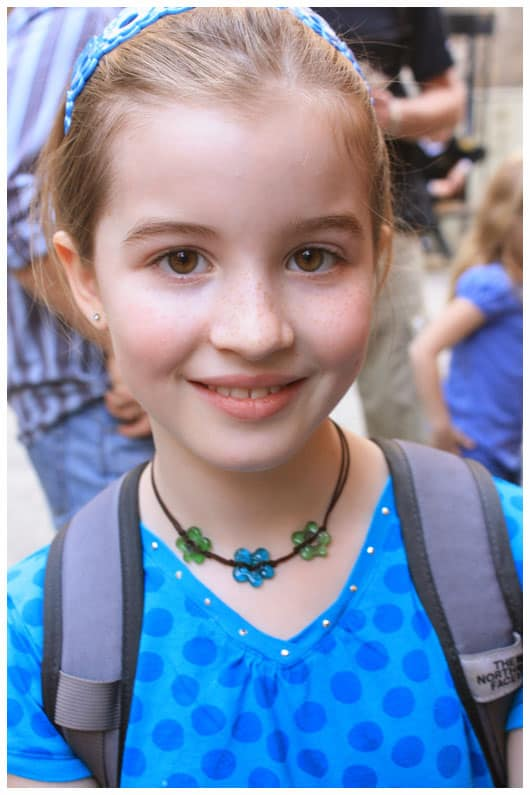 a girl wearing a blue and green flower necklace