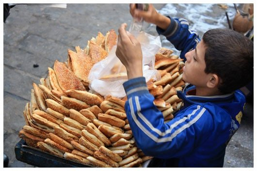 a young boy selling pastries