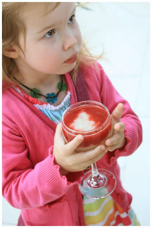 girl holding a glass of fresh guava and strawberry juice