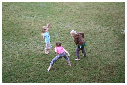 three children playing on the grass