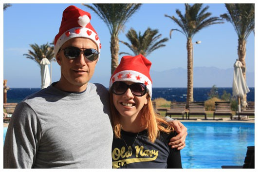 man and woman wearing santa hats