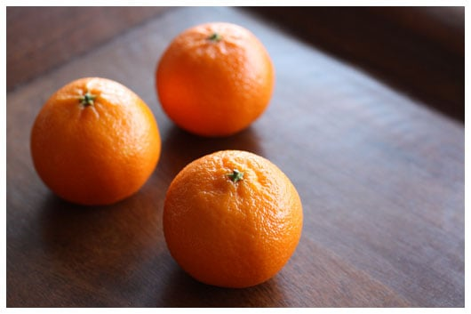 three clementines on a wood tray