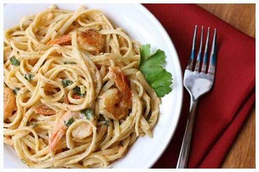 a plate of shrimp and tomato pasta