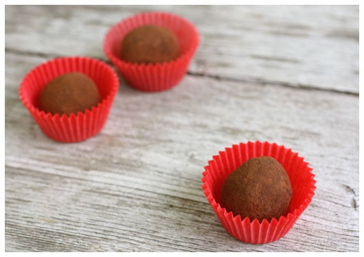 three truffles in red paper wrappers