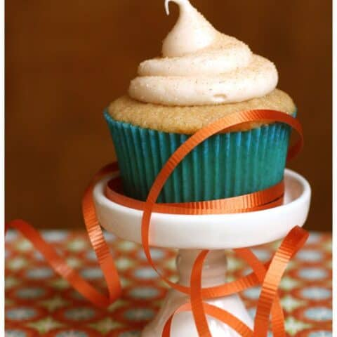 A Snickerdoodle Cupcake with Cinnamon Cream Cheese Frosting on a white stand