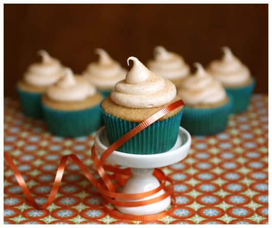 A Snickerdoodle Cupcake with Cream Cheese Frosting on a white stand with more cupcakes behind it