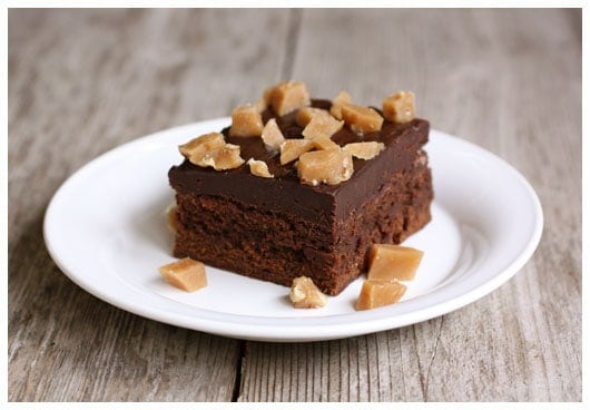 a piece of brownie with chocolate frosting and toffee pieces