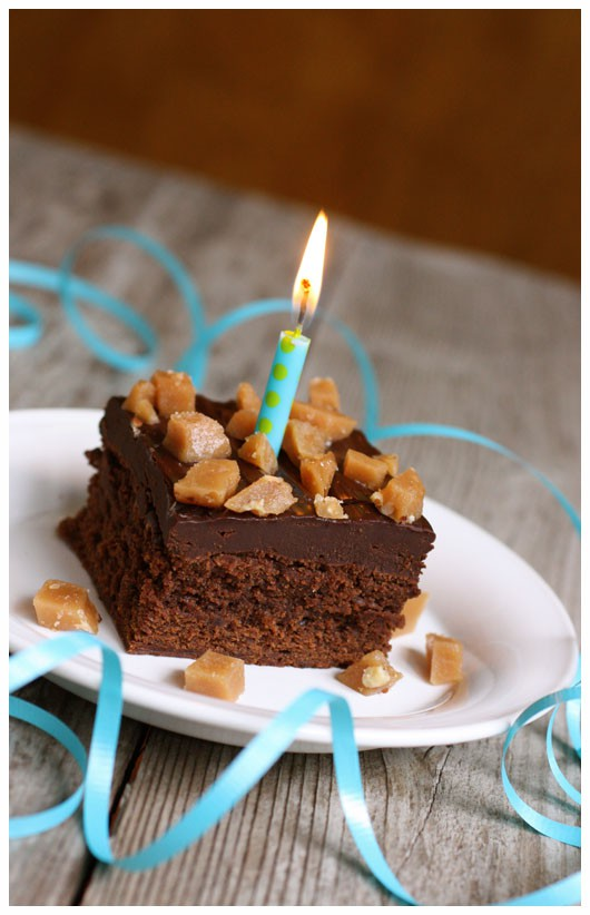 A slice of Toffee Brownie Cake on a white plate with blue ribbon