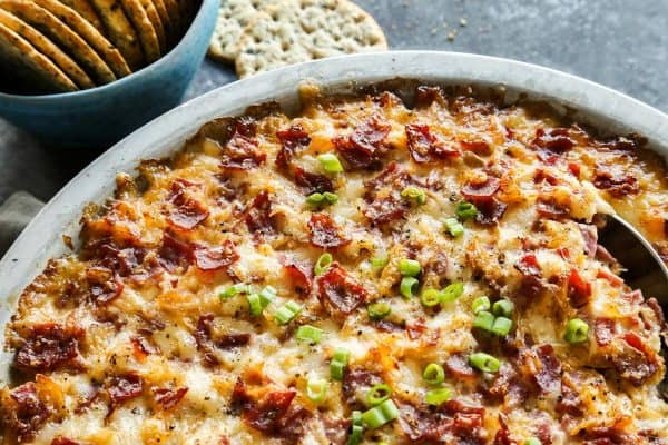 Reuben Dip from afarmgirlsdabbles.com - This hot reuben dip is like a deconstructed Reuben sandwich, all magnificently reborn into a baked ooey gooey cheesy dip. You'll love this appetizer! #reuben #dip #appetizer #cheese #sauerkraut #cornedbeef #beef